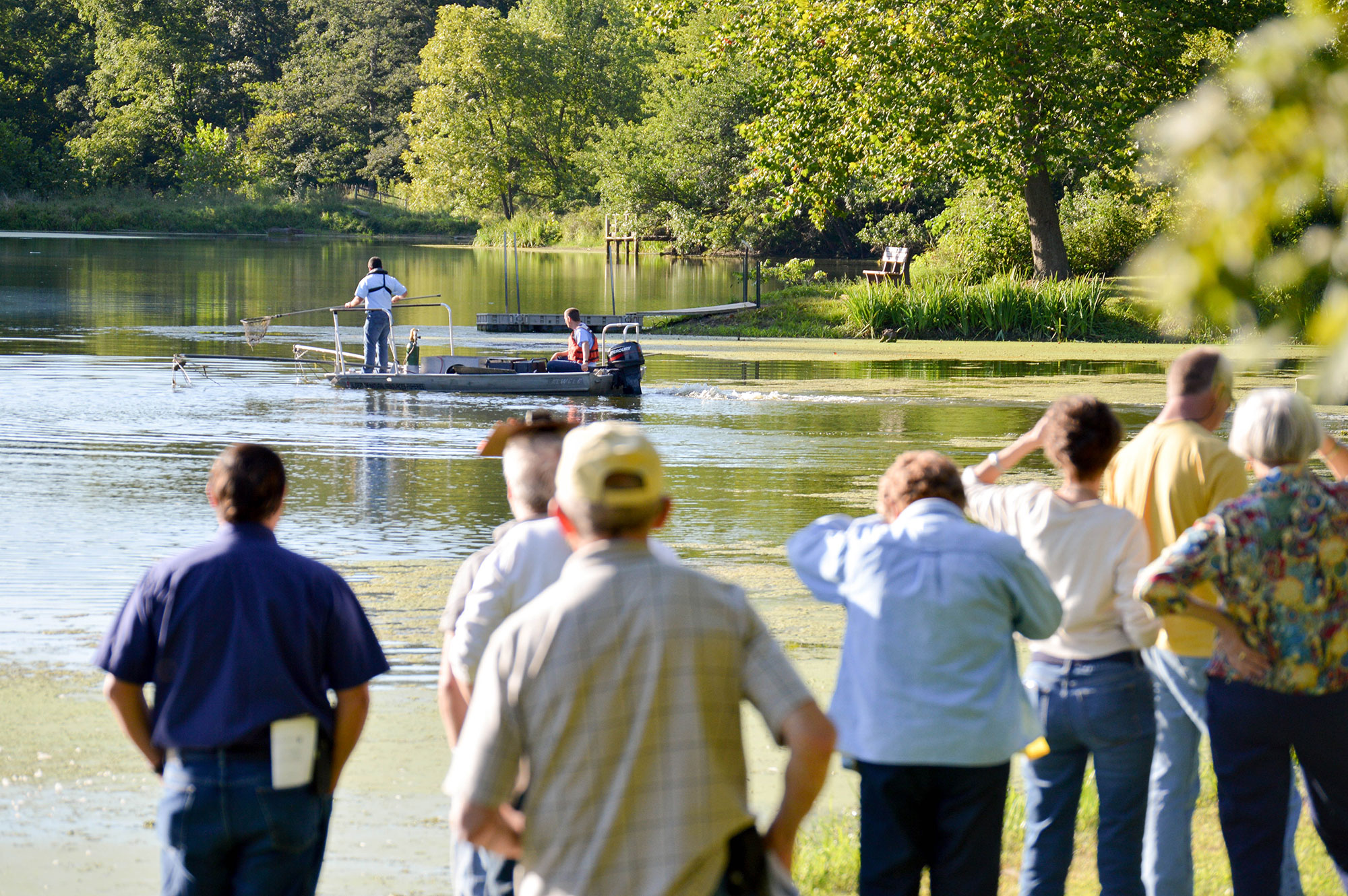 Crowd watches pond management in action during training.