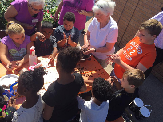 children work with Mater Gardeners on Pollinator Project