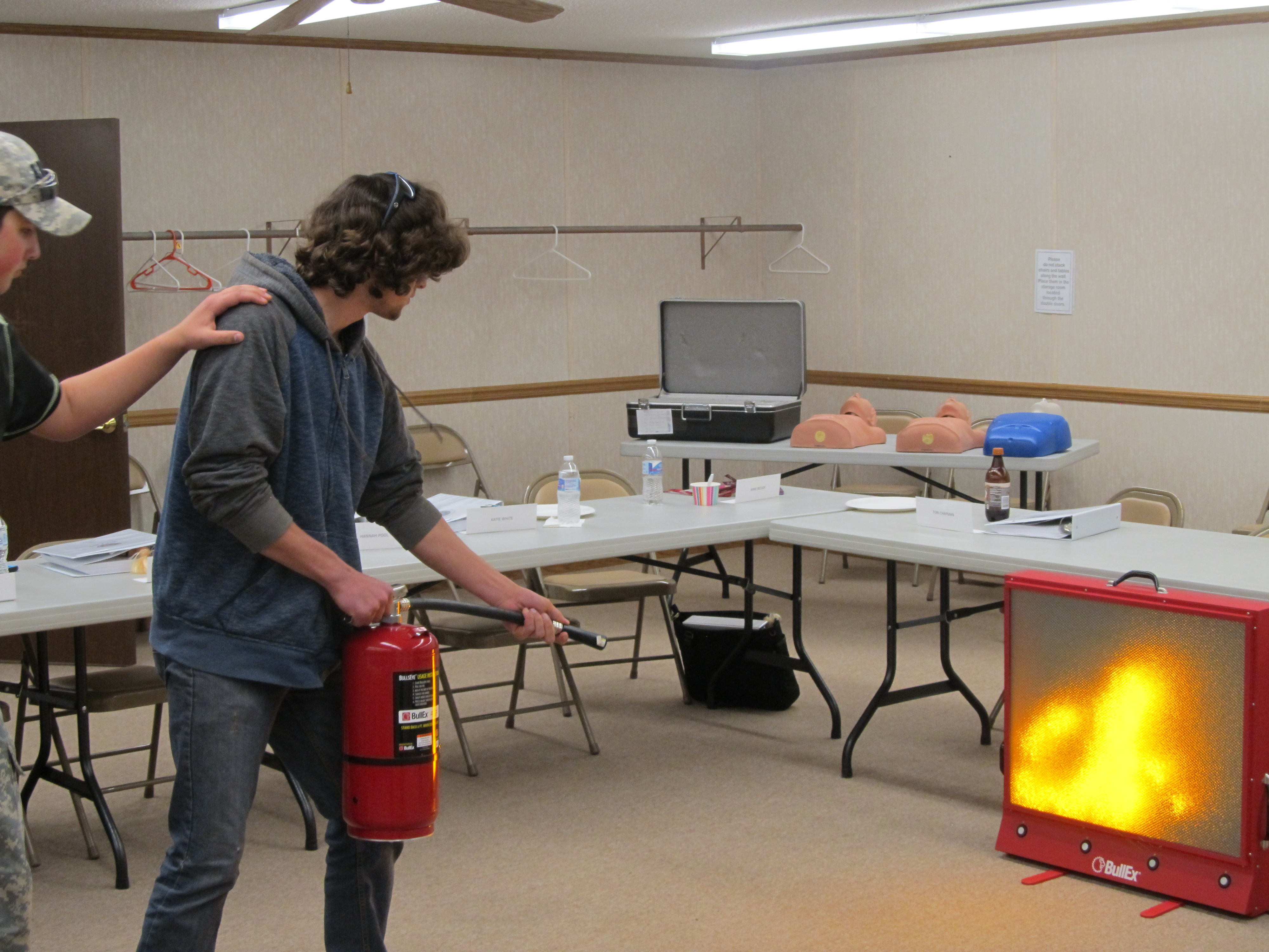 Teen practicing putting out a simulated fire with a fire extinguisher