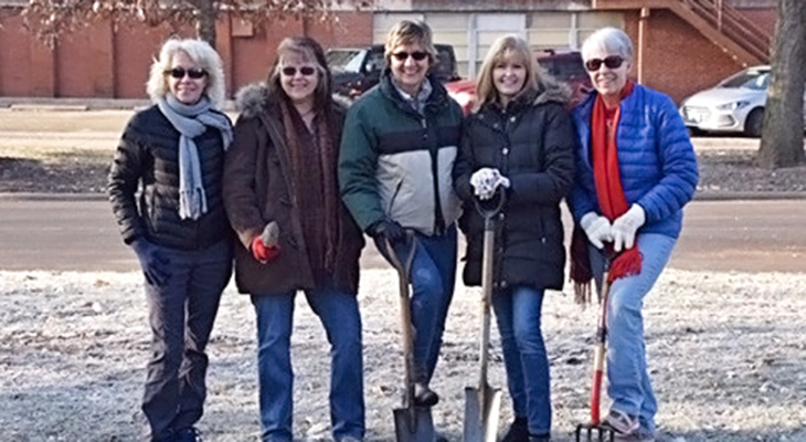 five Master Gardeners in winter coats holding shovels