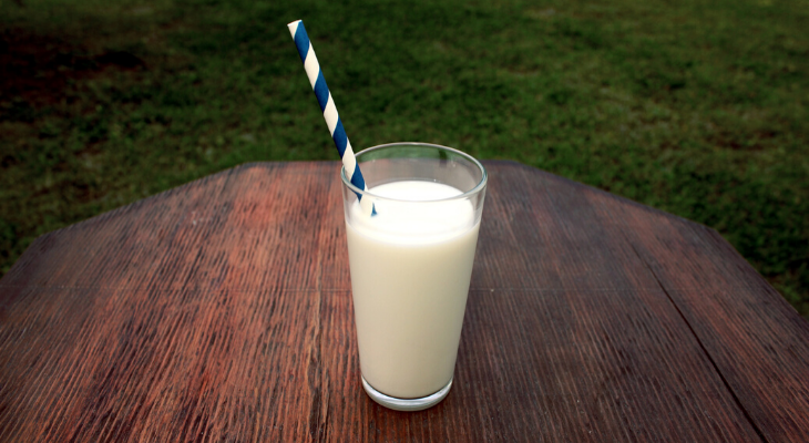 glass of milk with straw set on a picnic table