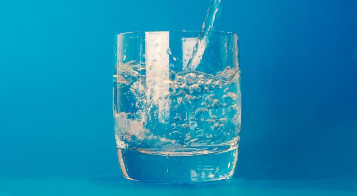 Blue background, glass in the middle of picture with water being poured into it.