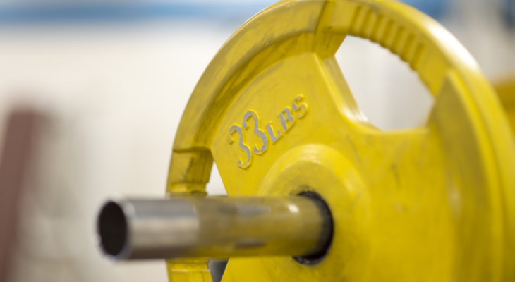 Yellow weight on a barbell.