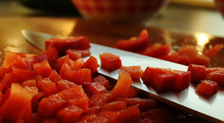 Chopped tomatoes surrounding a knife