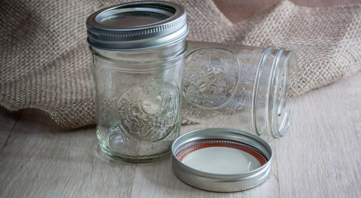Two glass canning jars on a table, one standing up with the lid on, the other tipped sideways with the lid on the table