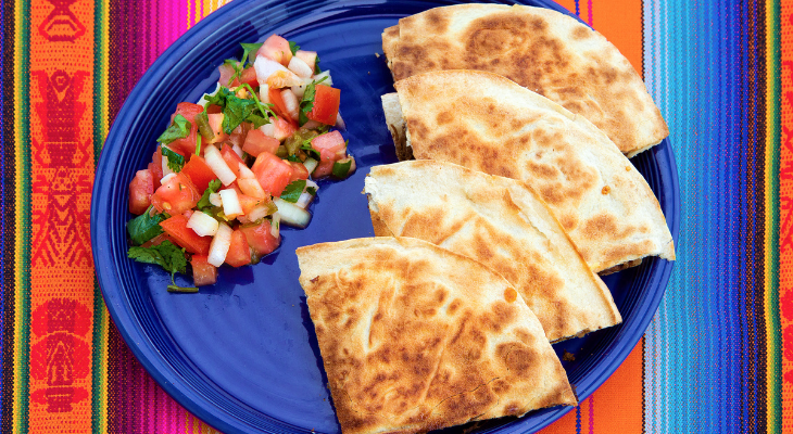 Four quesadilla slices and pico de gallo on a blue plate