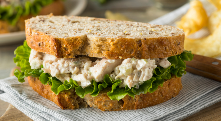 Chicken salad sandwich with lettuce and bread, set on a napkin on top of a table.