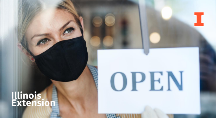 Business owner wearing a mask with an open store sign