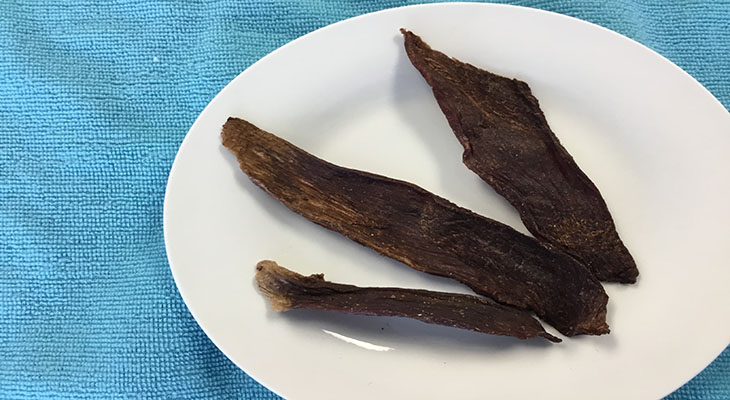 Three strips of jerky on white plate with blue background