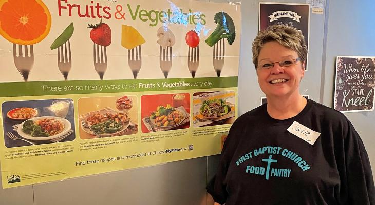 Julie Henderson, new First Baptist Food Pantry manager, with poster on fruits and vegetables