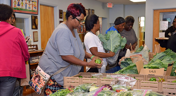 women serving fresh vegetables in food pantry line