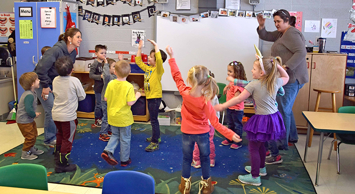 preschoolers dancing with their teachers