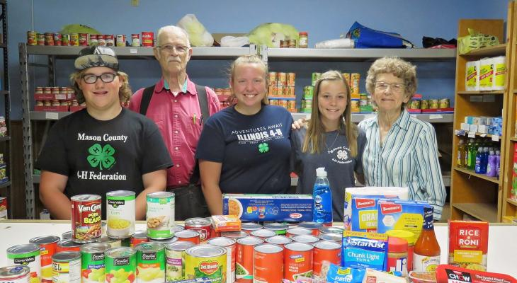 three teen 4-H members and two adults standing in food pantry with collection of food on counter