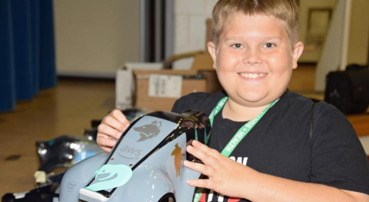 young boy holding AWS robotic car shell