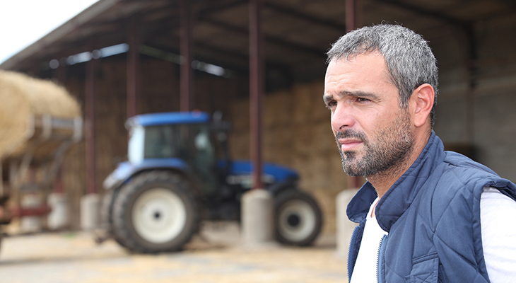 Worried looking middle-aged caucasian male in front of tractor with hay bales