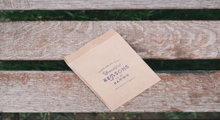 bench with paper bag that has inspirational saying on it
