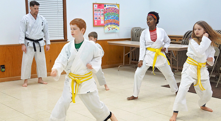 kids doing karate with teacher standing in background