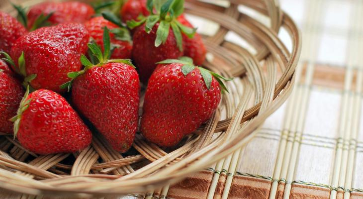 Strawberries in basket on plaid background