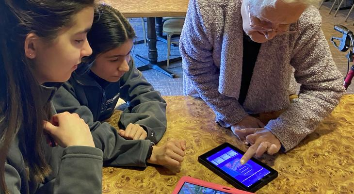 Teens help a senior citizen use an electronic device.