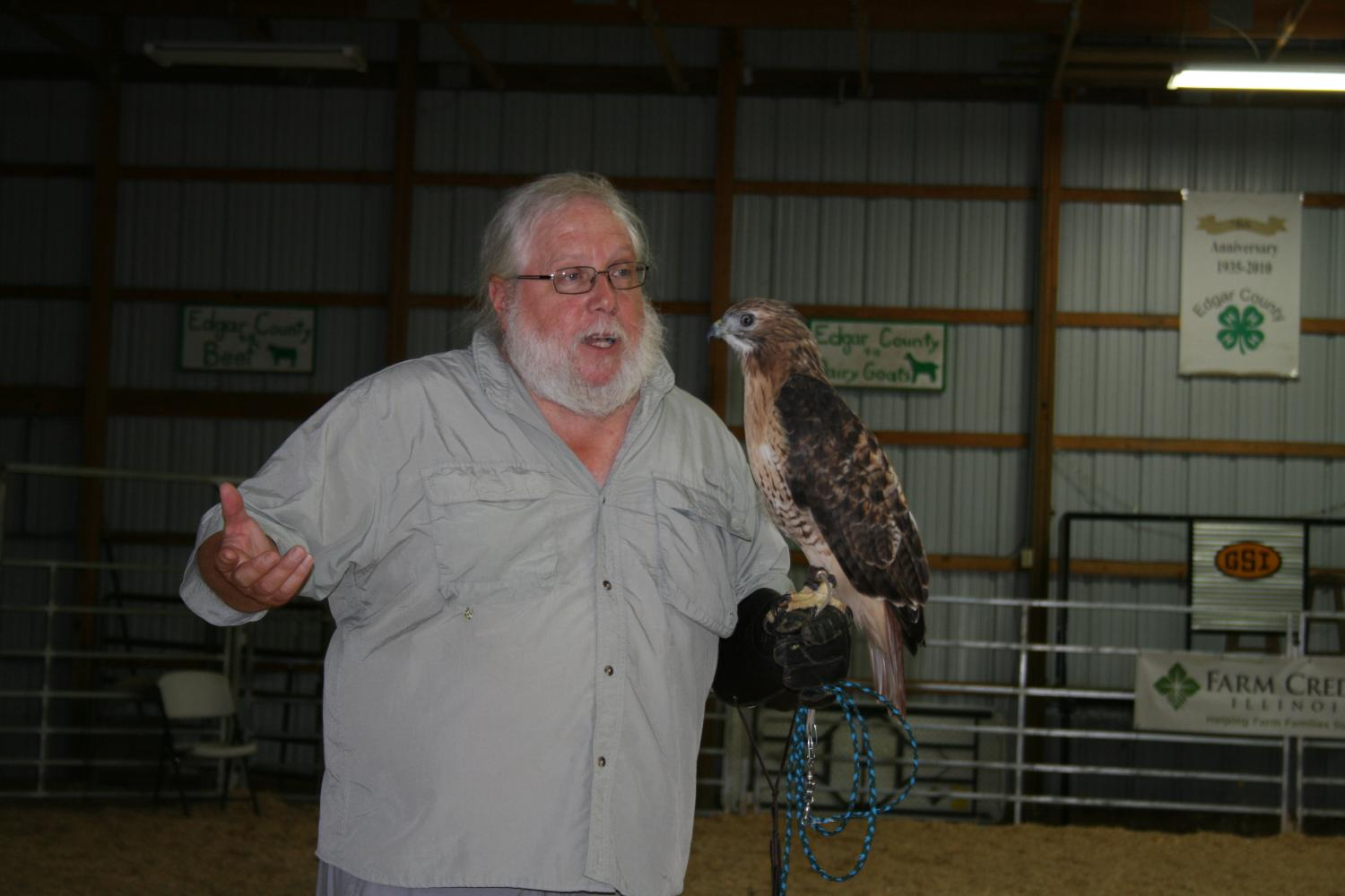 man holding a red-tailed hawk