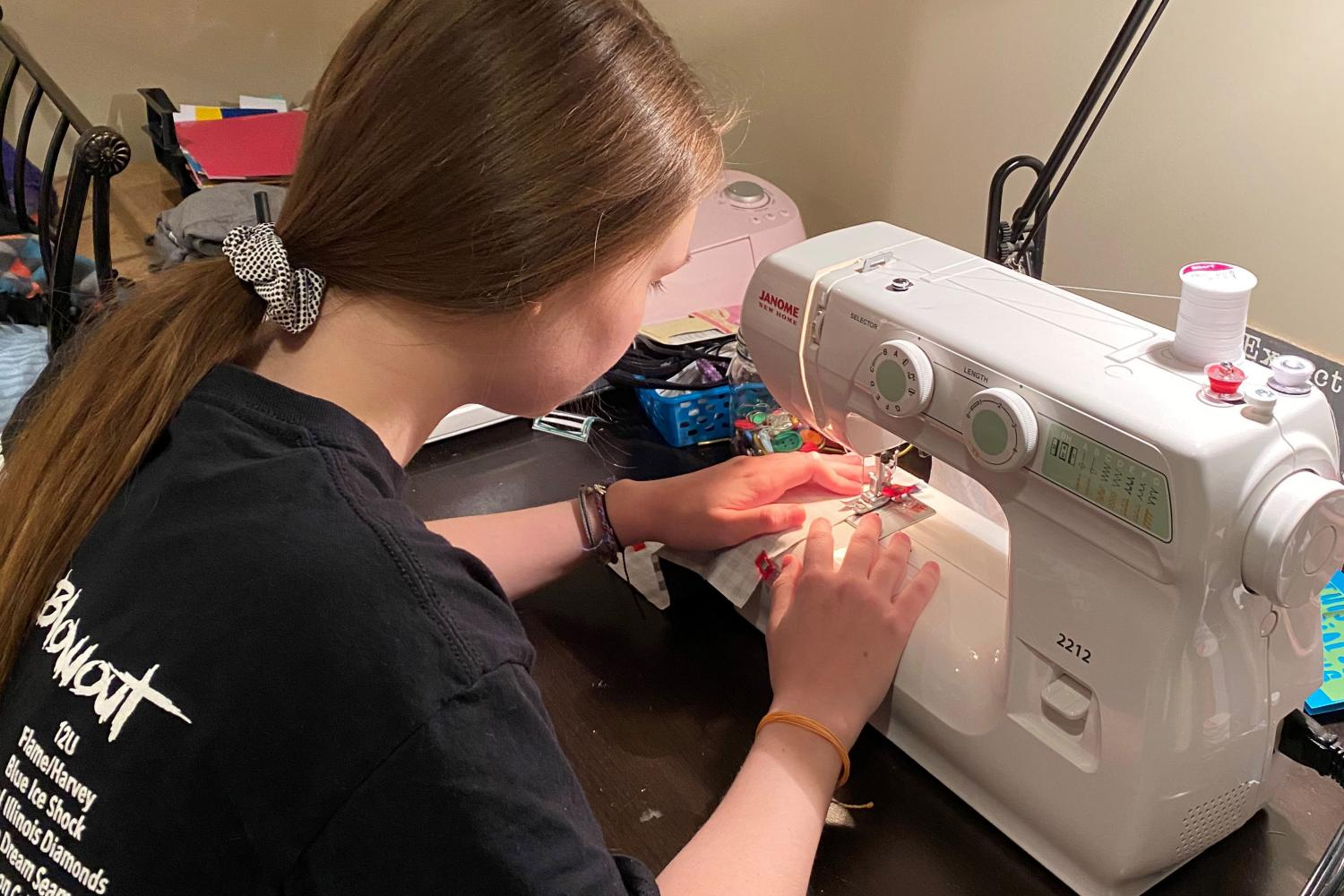 Young woman uses sewing machine to make mask
