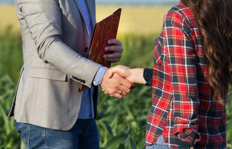 Woman farmer shaking hands with businessman in field.