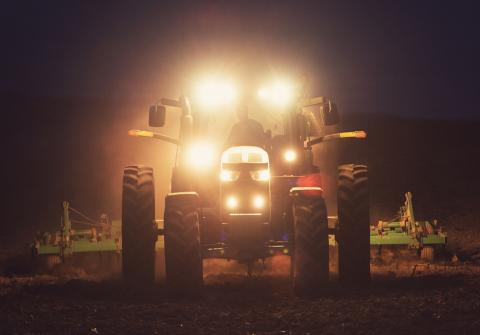 Tractor with lights on in dark