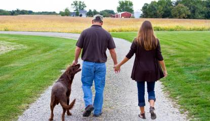 farm couple walks down gravel lane with brown Labrador retriever